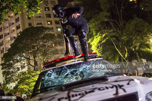 Protester in favor of former President Dilma Rousseff jumps on a police vehicle during a protest march on August 31, 2016 in Sao Paulo, Brazil....