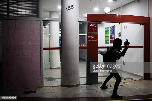 Protester in favor of former President Dilma Rousseff throws at a window during a protest march on August 31, 2016 in Sao Paulo, Brazil. Businesses...