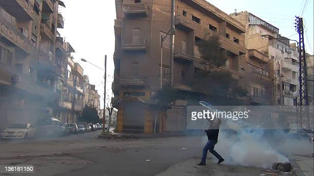 A protester in the flahspoint central Syrian city of Homs throws a tear gas bomb back towards security forces on December 27 2011 Syrian police used...