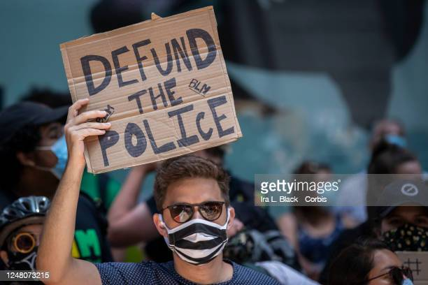 A protester in Times Square holds up a handmade sign that reads Defund The Police This was part of the Black Lives Matter New York protest that...