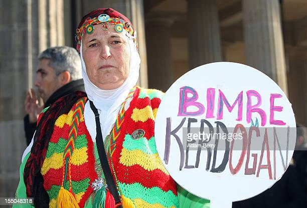 A protester in traditional Kurdish dress holds a sign reading Die Erdogan in Turkish while demonstrating in front of the Brandenburg Gate against the...