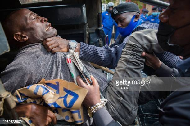 Protester is arrested and placed in the back of a vehicle by police officers as people demand the Kenyan government to take action for better living...