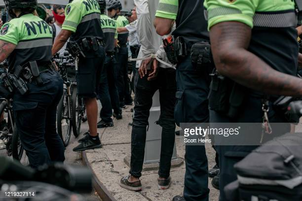 Protester is arrested by NYPD officers during a march against police brutality on June 11, 2020 in New York City. Demonstrations against systemic...