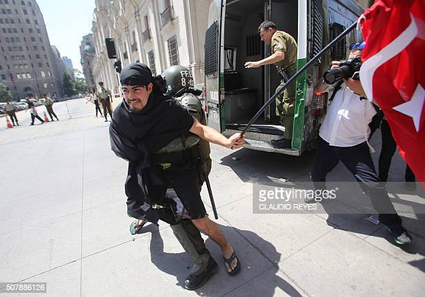 A protester is arrested by riot police in front of La Moneda Presidential Palace during a demonstration against Turkish President Recep Tayyip...