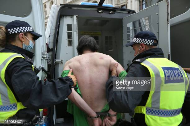 Protester is arrested for blocking the highway in Whitehall as part of a freedom demonstration on July 19, 2021 in London, England. Anti-lockdown...