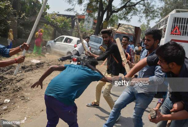 A protester is beaten by Indian students after members of the Dalit community and other 'low caste' groups threw bricks at their college during...