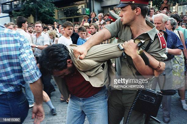 A protester is being grabbed by a policeman as he gathered along with two thousands demonstrators 21 August 1989 on Prague's Wenceslas Square to...