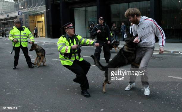 A protester is bitten by a police dog near to the Bank of England as anti capitalist and climate change activists demonstrate in the City of London...