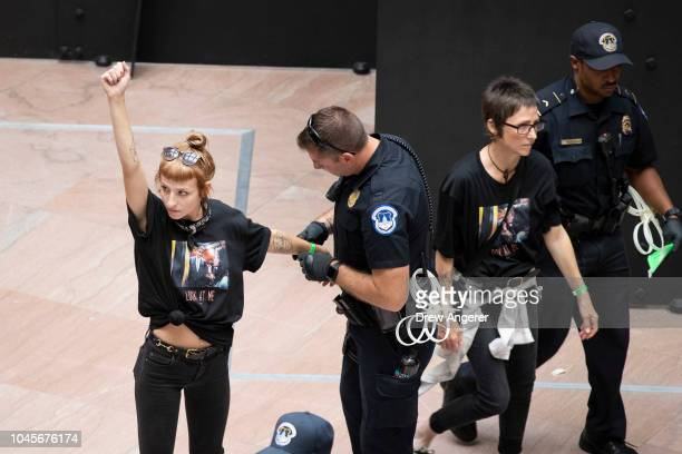 Protester is detained by Capitol Police officers as they rally against Supreme Court nominee Judge Brett Kavanaugh in the atrium of the Hart Senate...