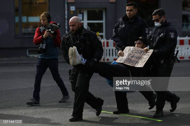 A protester is detained by police during a demonstration on May Day during the novel coronavirus crisis on May 1 2020 in Berlin Germany May Day...