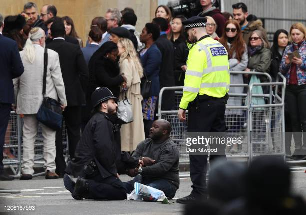 A protester is detained by police officers ahead of a visit by the Royal family to Westminster Abbey to attend the Commonwealth Day Service 2020 on...