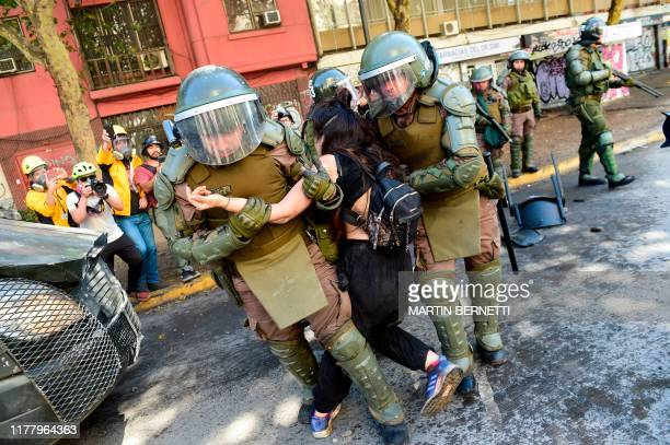 Protester is detained by riot police as people demonstrate in Santiago on October 24, 2019 after a week of street violence which erupted against a...