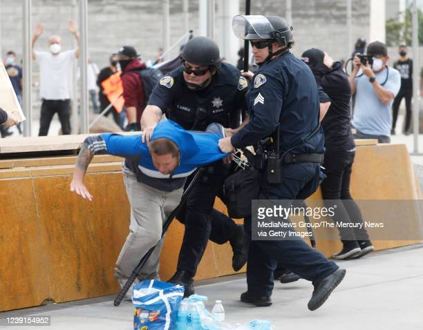 A protester is detained by San Jose Police officers at a protest of the killing of George Floyd outside of San Jose City Hall in downtown San Jose...