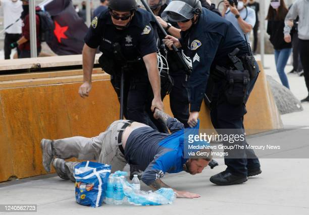 A protester is detained during a protest of the killing of George Floyd outside of San Jose City Hall in downtown San Jose Calif on Sunday May 31 2020