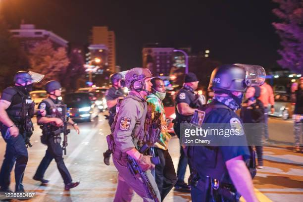 Protester is detained shortly after shots are fired at police, resulting in two injured officers, on September 23, 2020 in Louisville, Kentucky....