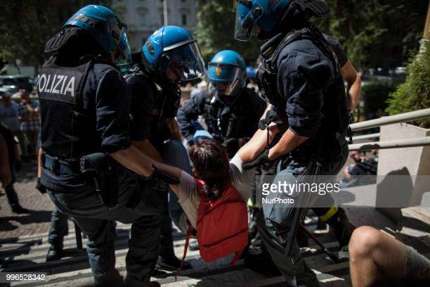 A protester is dragged away by Italian police outside the Ministry of Transport in Rome on July 11 2018 Dozens of 'We remain human' network activists...