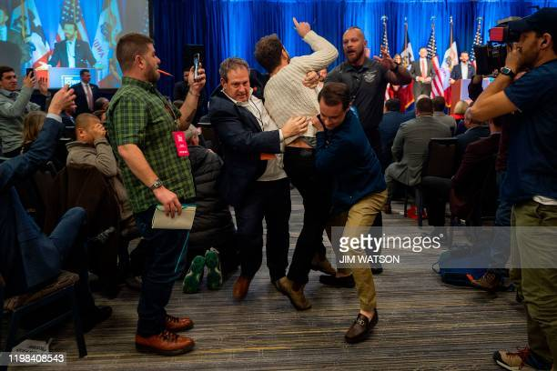 A protester is dragged from the room as Donald Trump Jr speaks with his brother Eric during a Keep Iowa Great press conference in Des Moines IA on...