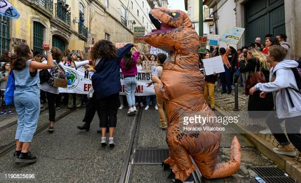 Protester is dressed in a dinosaur costume as demonstrators chant and hoist placards at a rally in support of the climate strike on November 29, 2019...