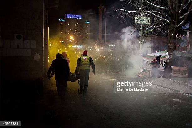 A protester is evacuated outside the Trade Unions building as the riot police launched an early morning intervention to partially clear Maidan Square...