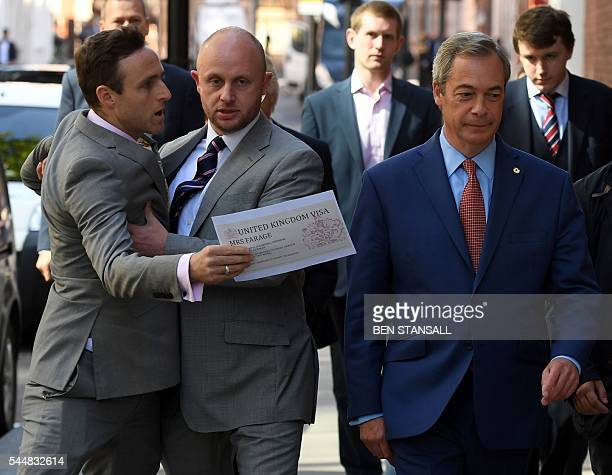A protester is held back as Leader of the United Kingdom Independence Party Nigel Farage arrives to make a speech in London on July 4 announcing that...