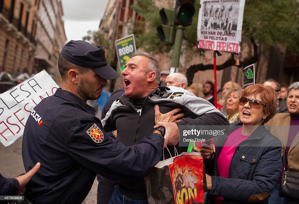 A protester is held back by a policeman at Madrid's High Court where Rodrigo Rato, former chairman of rescued bank Bankia and former head of the International Monetary Fund is scheduled to answer allegations of misusing company credit cards on October 16, 2014 in Madrid Spain. Judge Fernando Andreu is questioning Rato along with former Bankia chief Miguel Blesa and former financial director Ildefonso Sanchez Barcoj.