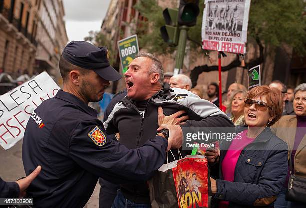 A protester is held back by a policeman at Madrid's High Court where Rodrigo Rato former chairman of rescued bank Bankia and former head of the...