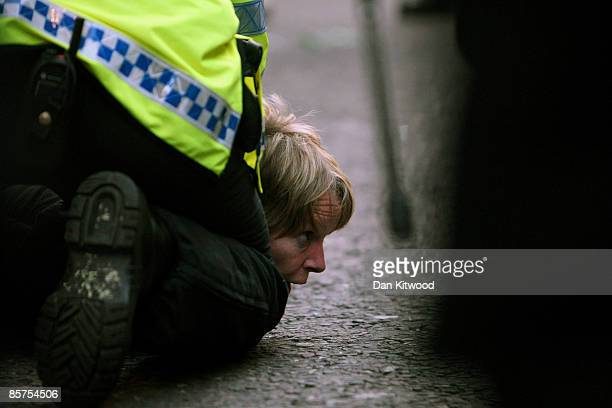 A protester is held down by police as anti capitalist and climate change activists demonstrate in the City of London on April 1 2009 in London...