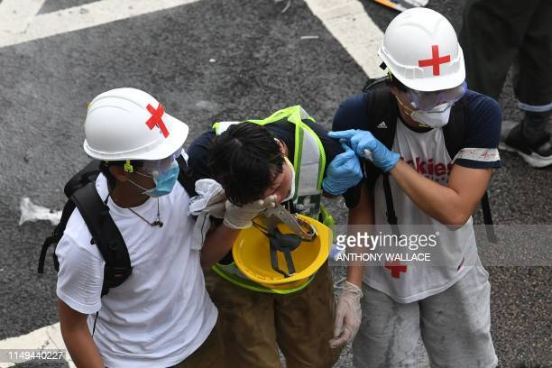 TOPSHOT A protester is helped by medical volunteers after being hit by tear gas fired by the police during a rally against a controversial...