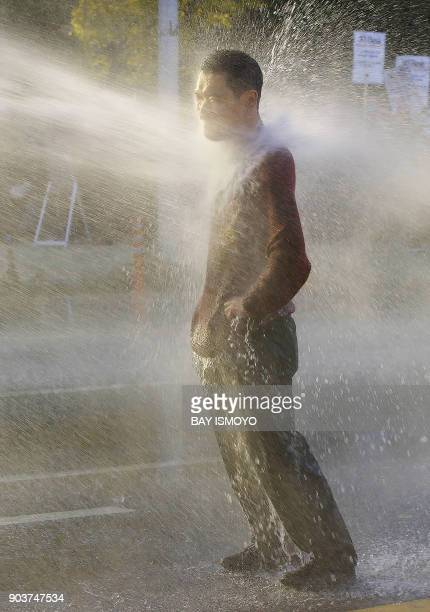 A protester is hit by a water jet as antiriot police use water cannon to disparse an antiAPEC and antiBush rally on a street in downtown Busan 18...