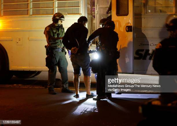 A protester is loaded into Santa Clara County Sheriffs bus after being detained for breaking curfew by the San Jose Police Department and the...