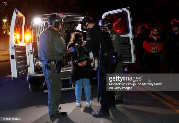 A protester is loaded into the back of a Santa Clara County Sheriffs van after being detained for breaking curfew by the San Jose Police Department...