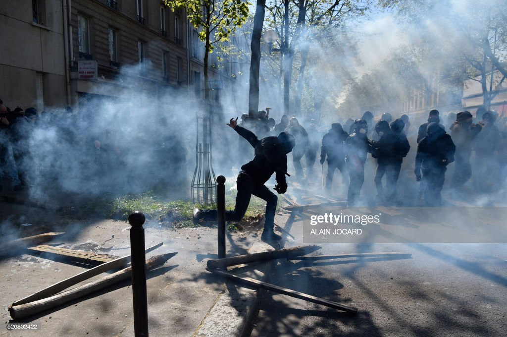 TOPSHOT - A protester is pictured during a clash with French anti riot police during the traditional May Day demonstration in Paris on May 1, 2016. / AFP / ALAIN