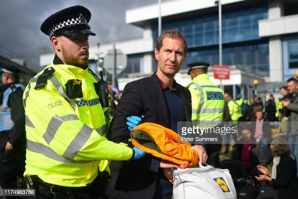 Protester is removed by police as climate change action group Extinction Rebellion stage a protest at London City Airport during the fourth day of...