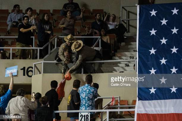 A protester is restrained by police officers after displaying a Trump flag at a campaign rally for Democratic Presidential Candidate Sen Bernie...