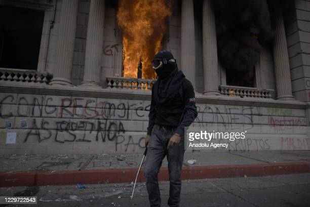 Protester is seen as demonstrators set the Congress building on fire during a protest against the President of Guatemala Alejandro Giammattei, in...