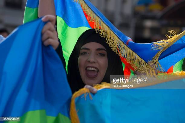 A protester is seen covered in the flags of the Amazigh people Protest against a sentence of 20 years imprisonment to the rifan leaders in Morocco...