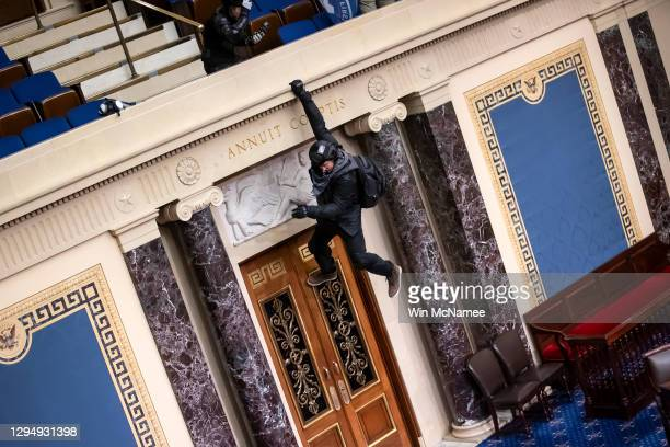Protester is seen hanging from the balcony in the Senate Chamber on January 06, 2021 in Washington, DC. Congress held a joint session today to ratify...