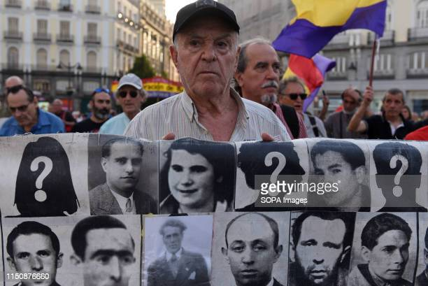 A protester is seen holding a banner with pictures of people who went missing during the Spanish dictatorship of Francisco Franco Around 1000 people...
