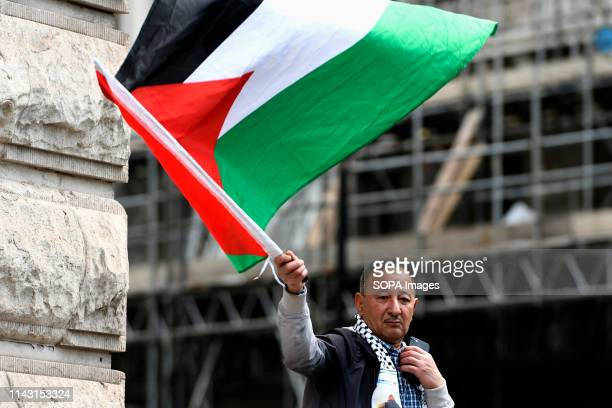 A protester is seen holding a Palestinian flag during the demonstration Palestinian human rights activist Ahed Tamimi joined the National demo for...