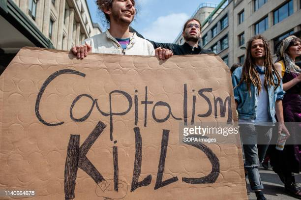 A protester is seen holding a placard that says Capitalism kills during the demonstration Several trade unions gathered at the Place Poelaert close...