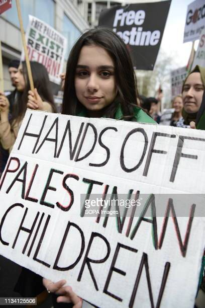 A protester is seen holding a placard that says Hands off Palestinian children during the Exist Resist Return Rally for Palestine in London People...