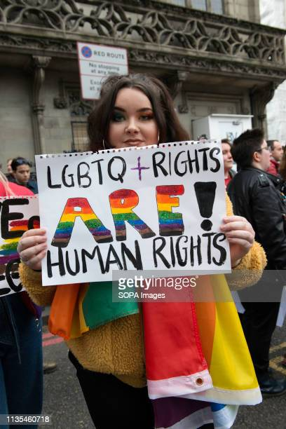 A protester is seen holding a placard that says LGBTQ Rights are human rights during the demonstration Protesters gathered outside of the luxury...