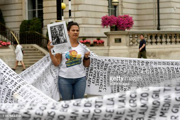 A protester is seen holding a placard with the photo of Jonathan Eduardo Landines who was a deadly victim of an explosion that occurred in Dagua...