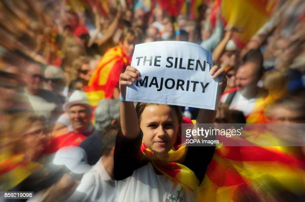 A protester is seen holding a placard writting on it 'silent majority' Thousands of people protested on Sunday in Barcelona against the independence...