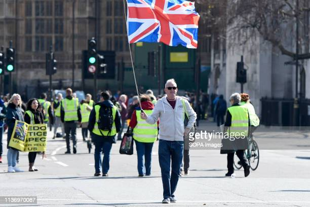 A protester is seen holding an Union jack flag during the demonstration Protesters gathered at Parliament Square and marched to different places...