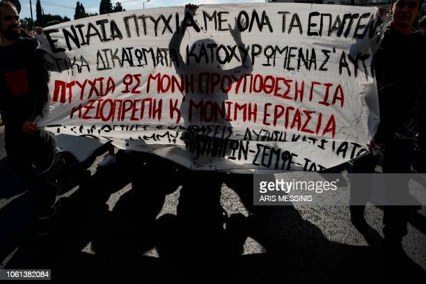 A protester is seen in silhouette behind a banner during a demonstration marking the civil servants 24hour strike against government's economic...