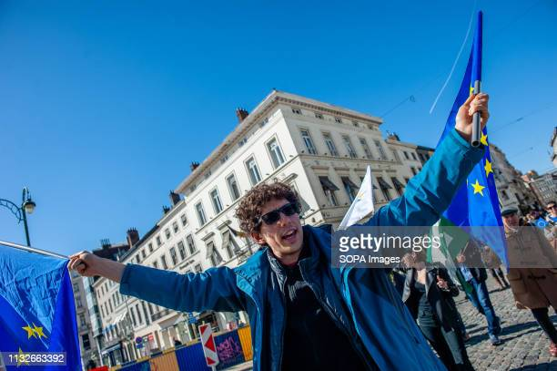 A protester is seen shouting slogans while holding flags of the EU during the protest A day before the anniversary of the founding Treaty of the...