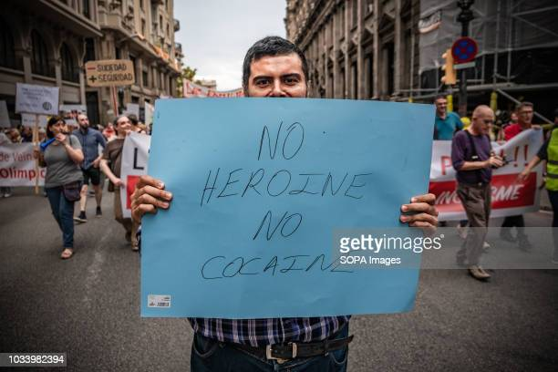 A protester is seen showing a poster against drug trafficking in the city of Barcelona during the protest by various associations of neighbors and...