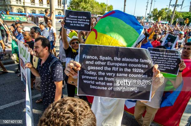 Protester is seen showing a poster during the demonstration. More than 500 people from the Rif community in Barcelona have demonstrated to show their...