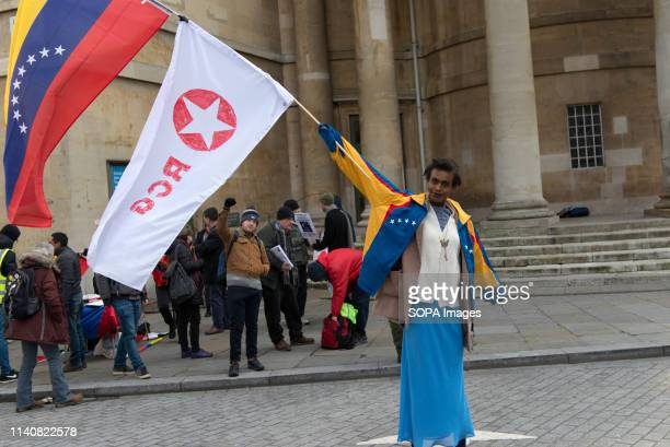 A protester is seen waving a Venezuelan flag and The Revolutionary Communist Group flag during the Hands off Venezuela protest in London Protesters...
